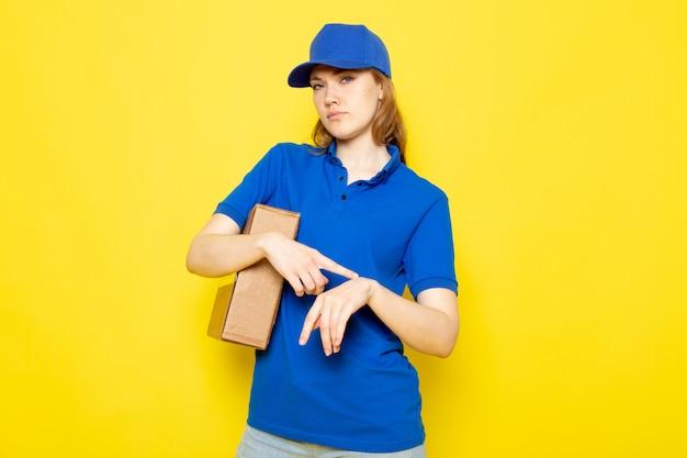 Een vooraanzicht vrouwelijke aantrekkelijke koerier in blauw poloshirt blauw glb en jeans die pakket houden wat betreft haar pols op de gele achtergrondvoedseldienst Gratis Foto