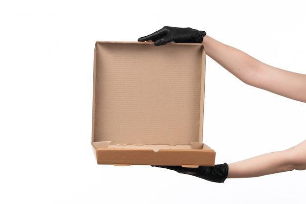 Een vooraanzicht vrouwelijke hand die een lege leveringsdoos op wit houdt Gratis Foto