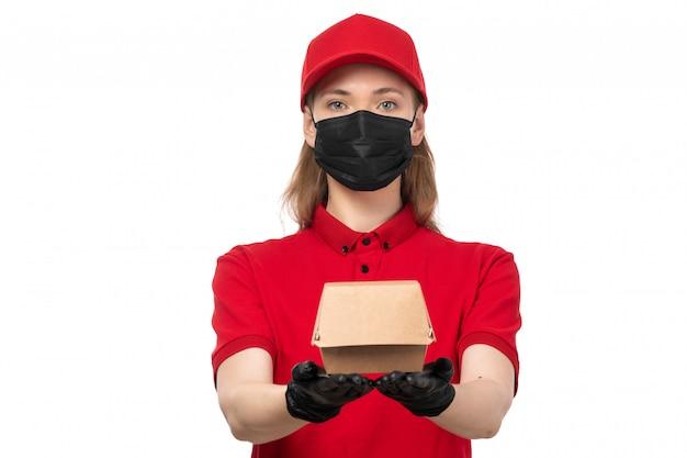 Een vooraanzicht vrouwelijke koerier in rode overhemd rode glb zwarte handschoenen en het zwarte pakket van de maskerholding op wit Gratis Foto
