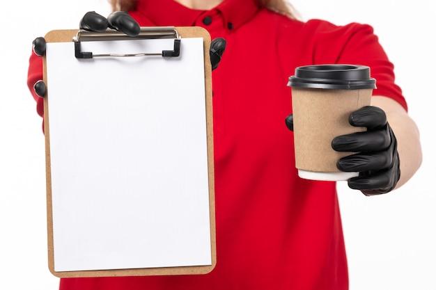 Een vooraanzicht vrouwelijke koerier in rode overhemd zwarte handschoenen die koffie en document op wit houden Gratis Foto