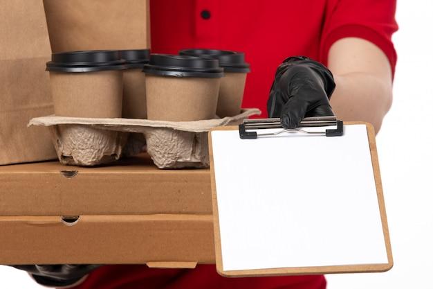 Een vooraanzicht vrouwelijke koerier in rood overhemd rode pet zwarte handschoenen en zwart masker met koffiekopjes en voedselpakketten met kladblok Gratis Foto