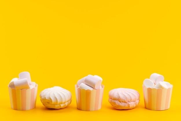Een vooraanzicht witte marshmallows in papieren verpakkingen samen met witte schuimgebakjes op geel Gratis Foto