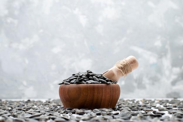 Een vooraanzicht zwarte zonnebloempitten verse en smakelijke graan zonnebloempitten snackolie Gratis Foto