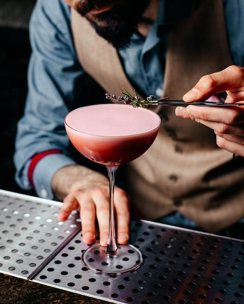 Een vooraanzichtbarman die cocktail op de cocktail van het het sapdrankje van het barbureau voorbereidt Gratis Foto
