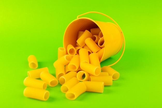 Een vooraanzichtdeegwaren binnen mand vormden ruwe binnen gele mand op de groene italiaanse spaghetti van het achtergrondmaaltijdvoedsel Gratis Foto