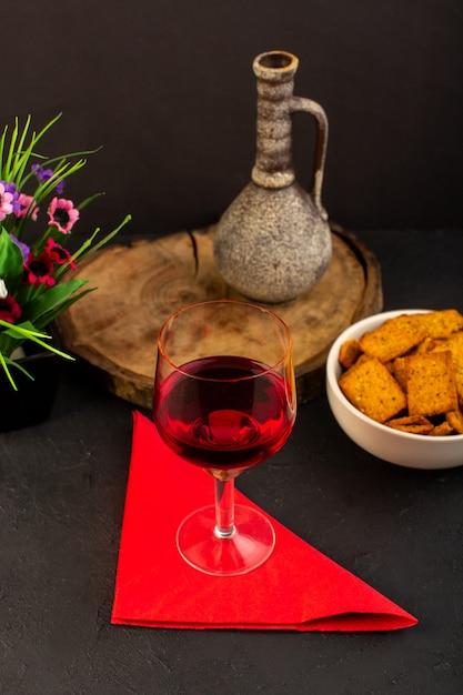 Een vooraanzichtglas wijn samen met bloem en chips binnen plaat op donker bureau Gratis Foto