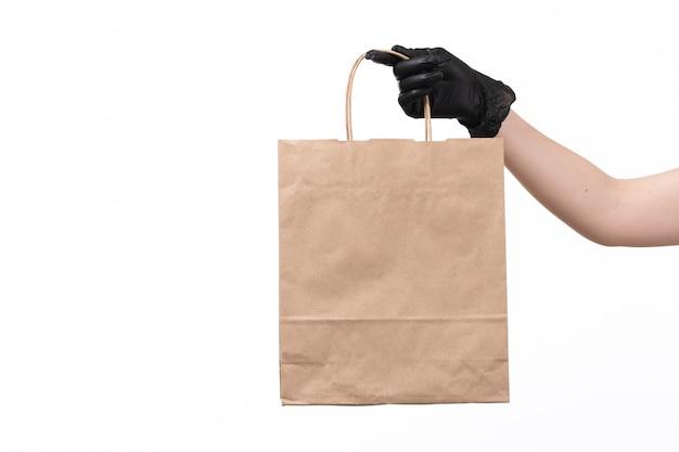 Een vooraanzichtvrouw dient het zwarte document van de handschoenholding voedselpakket op wit in Gratis Foto