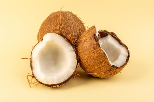 Een voorzijde sloot omhoog kokosnoten gesneden melkachtige verse zacht die op de room gekleurde tropische noot van het achtergrond tropische exotische fruit wordt geïsoleerd Gratis Foto