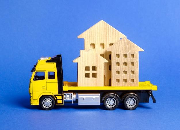 Een vrachtwagen vervoert huizen. concept van transport en vrachtverzending, verhuisbedrijf Premium Foto