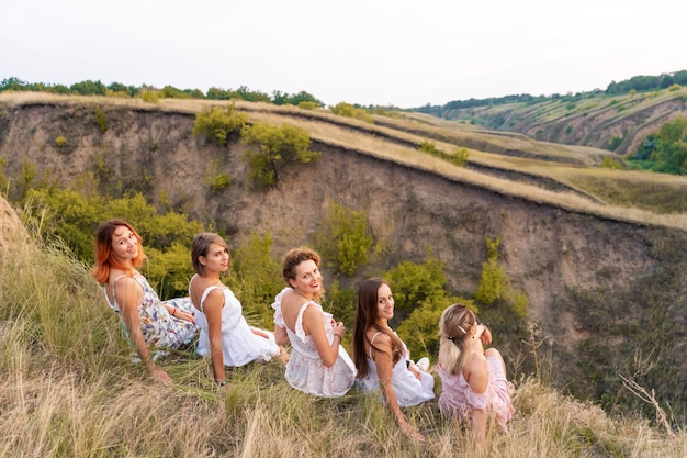 Een vrolijk gezelschap van mooie vriendinnen geniet bij zonsondergang van een schilderachtig panorama van de groene heuvels Premium Foto