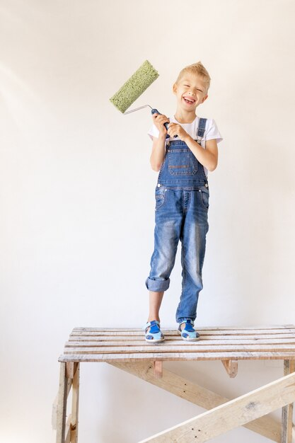 Een vrolijk kind zit op een bouwladder in een appartement met witte muren en een roller in zijn handen en toont een duim omhoog, een plek voor tekst, het concept van reparatie Premium Foto