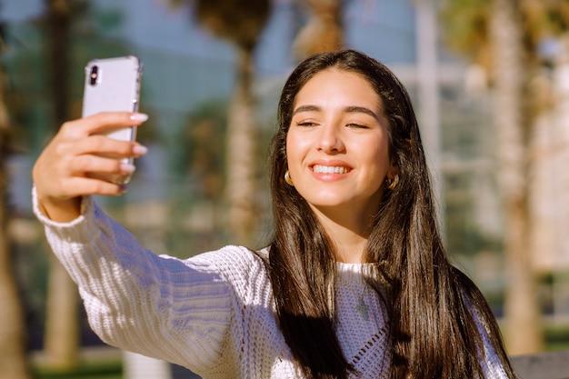 Een vrolijke brunette met een brede glimlach die een selfie doet Gratis Foto