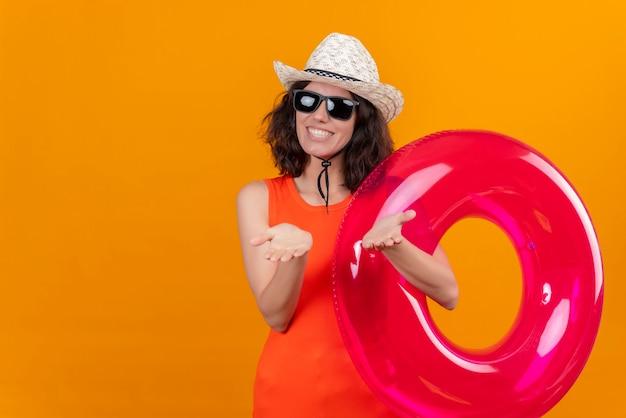 Een vrolijke en tevreden jonge vrouw met kort haar in een oranje overhemd met een zonnehoed en een zonnebril met opblaasbare ring Gratis Foto