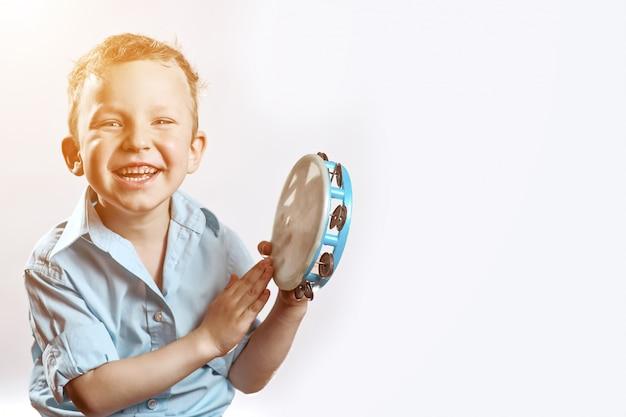 Een vrolijke jongen in een blauw shirt met een tamboerijn en glimlachen Premium Foto