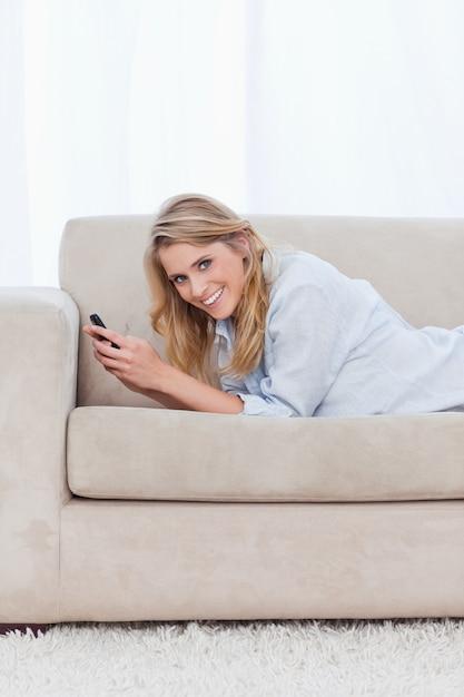 Een vrouw die bij de camera glimlacht houdt een mobiele telefoon Premium Foto