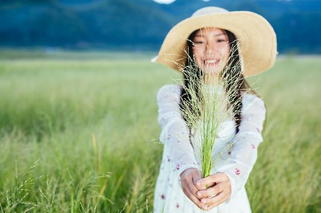 Een vrouw die een gras in haar handen houdt op een prachtig grasveld met een berg. Gratis Foto