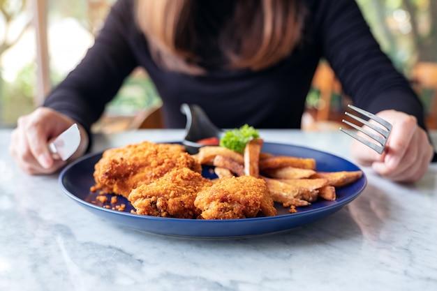 Een vrouw die een mes en een vork gebruikt om gebraden kip en patat in een restaurant te eten Premium Foto