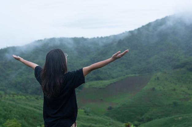 Een vrouw die midden op de berg staat met een verfrissende houding Gratis Foto