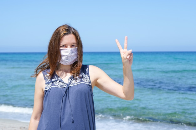 Een vrouw die op het zand op het strand staat met vingers in de overwinning en het masker voor de pandemie van covid-19 coronavirus Premium Foto