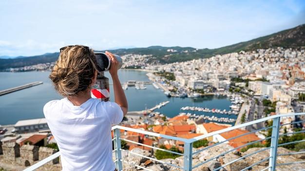 Een vrouw die stationaire verrekijker onderzoekt in kavala, griekenland Gratis Foto
