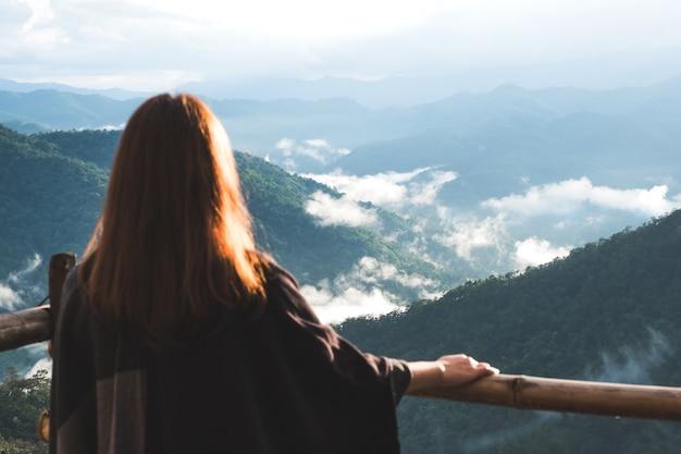 Een vrouw die zich alleen op balkon bevindt dat bergen op mistige dag met blauwe hemel in de ochtend bekijkt Premium Foto
