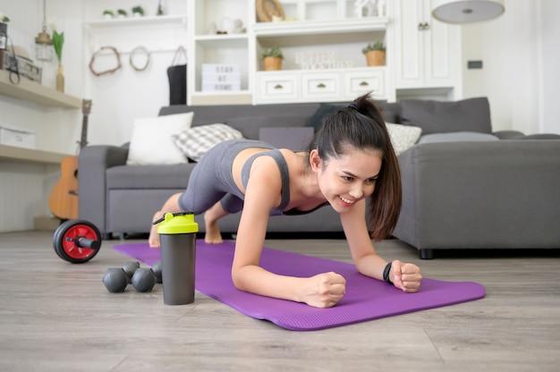 Een vrouw doet yoga plank en kijkt naar online training tutorials op haar laptop in de woonkamer, fitnesstraining thuis, gezondheidszorg technologie concept. Premium Foto