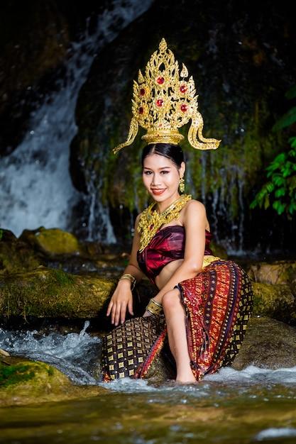 Een vrouw gekleed met een oude thaise jurk bij de waterval. Gratis Foto