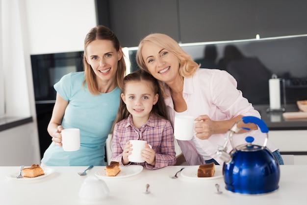 Een vrouw, haar moeder en dochter drinken thee. Premium Foto