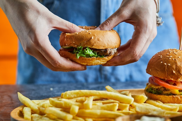 Een vrouw hand met cheeseburger met gebakken aardappel, ketchup, mayonaise Gratis Foto
