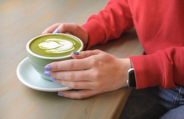 Een vrouw in een café dat een groene matcha latte met veganistische plantaardige melk drinkt Premium Foto