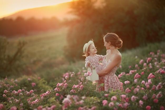 Een vrouw in een retro jurk met haar dochter 5 jaar oud wandelen in het voorjaar in een veld met rozen Premium Foto