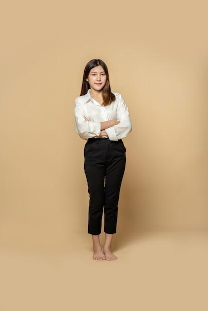 Een vrouw in een wit overhemd en een zwarte broek staat met haar armen over elkaar Gratis Foto