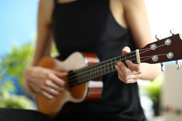 Een vrouw in een zwarte jurk leert ukelele spelen. meisje stemt een miniatuurgitaar voor een concert Premium Foto