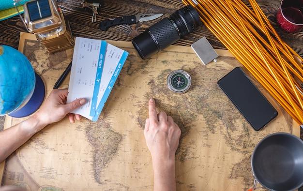 Een vrouw kiest een plek voor haar volgende reis door naar een kaart van de wereld op een houten tafel met kampeeruitrusting te wijzen Premium Foto