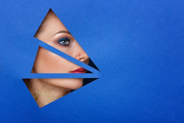 Een vrouw kijkt in het gat het papier, mooie make-up. Premium Foto