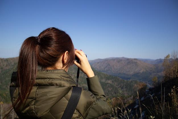 Een vrouw kijkt met een verrekijker naar het prachtige landschap van de bergen vanaf het observatiedek Premium Foto