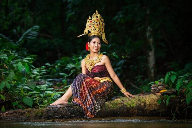 Een vrouw kleedde zich met een oude thaise jurk aan de waterval. Gratis Foto