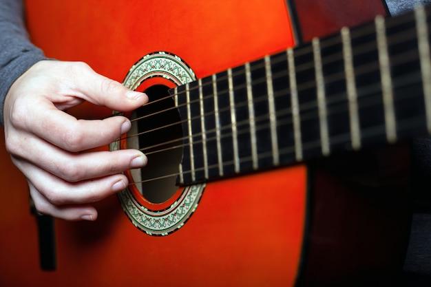 Een vrouw leert een klassieke zes-snarige akoestische gitaar spelen. detailopname. Premium Foto