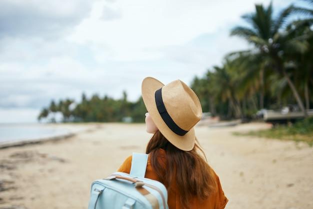 Een vrouw met een blauwe rugzak in een gele jurk en hoed loopt langs de oceaan langs het zand met palmbomen Premium Foto