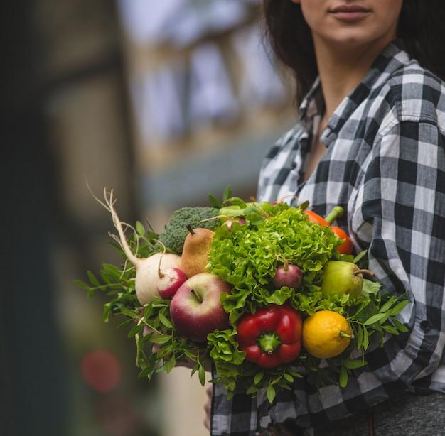Een vrouw met een boeket van groenten en fruit in de hand op straat Gratis Foto
