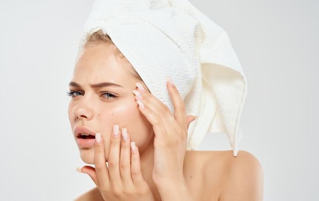 Een vrouw met een handdoek op haar hoofd knijpt acne op haar gezicht probleemhuid cosmetologie dermatologie. Premium Foto