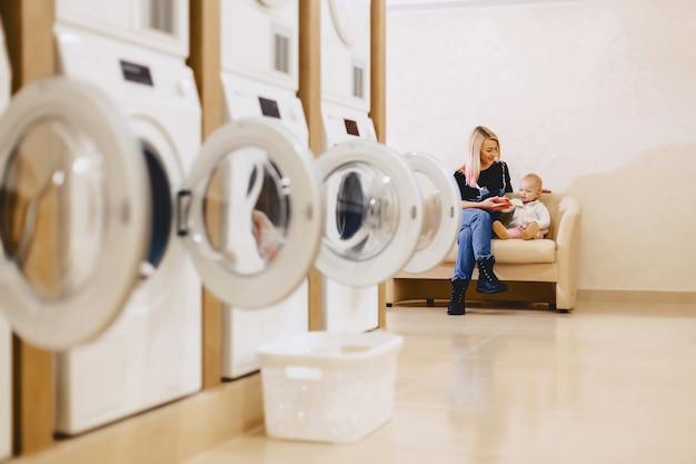 Een vrouw met een kind zit in de wacht op de bank in de wasserij Premium Foto