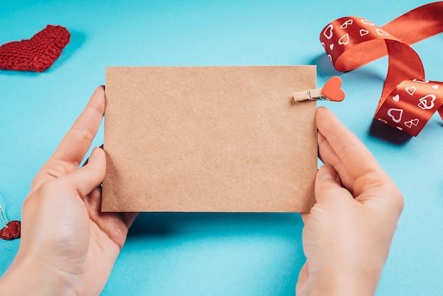 Een vrouw met een kraftpapier-brief met een hart in haar handen voor valentijnsdag Premium Foto