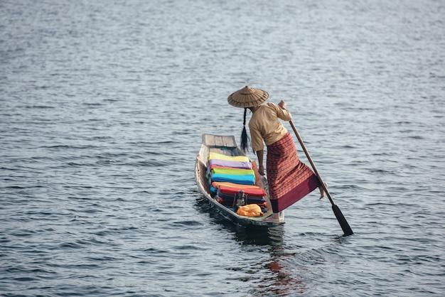 Een vrouw met handgemaakte kleurrijke lotusstoffen op haar boot in het dorp dain khone, aan het inlemeer, myanmar. Premium Foto