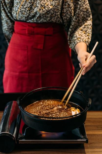 Een vrouw met kimono roerbak zeldzame plak wagyu a5-rundvlees in sukiyaki shoyu-soep met stokjes. Premium Foto
