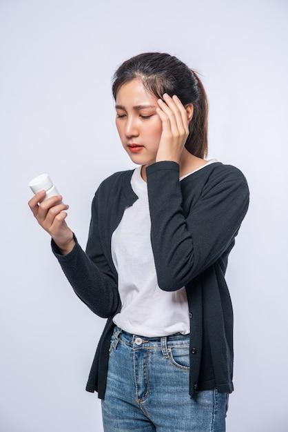 Een vrouw met pijn in haar hand houdt een medicijnflesje vast en de andere hand maar op haar hoofd Gratis Foto