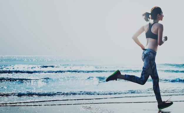 Een vrouw rent op het strand Premium Foto