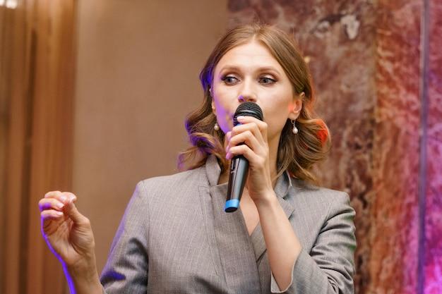 Een vrouw spreekt in een microfoon, geeft een lezing over zaken. conferentie training seminar zakelijke presentatie publieksvergadering. Premium Foto