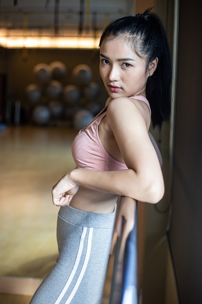 Een vrouw stond ontspannen, handen op een stalen rail in de sportschool. Gratis Foto