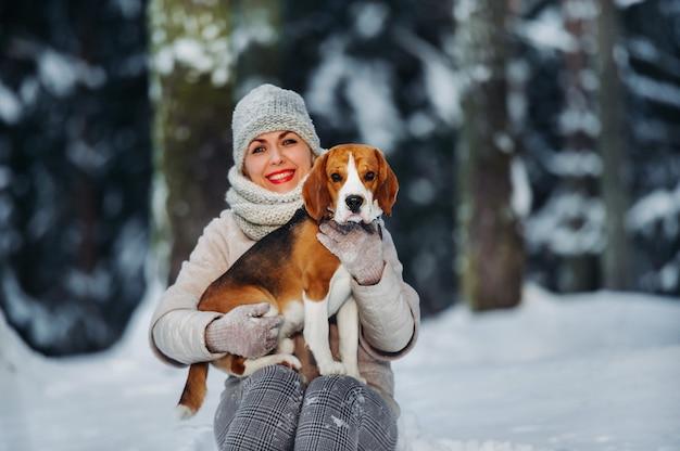 Een vrouw tijdens een wandeling met haar hond in het winterbos. meesteres en hondenspel in het besneeuwde bos. Premium Foto